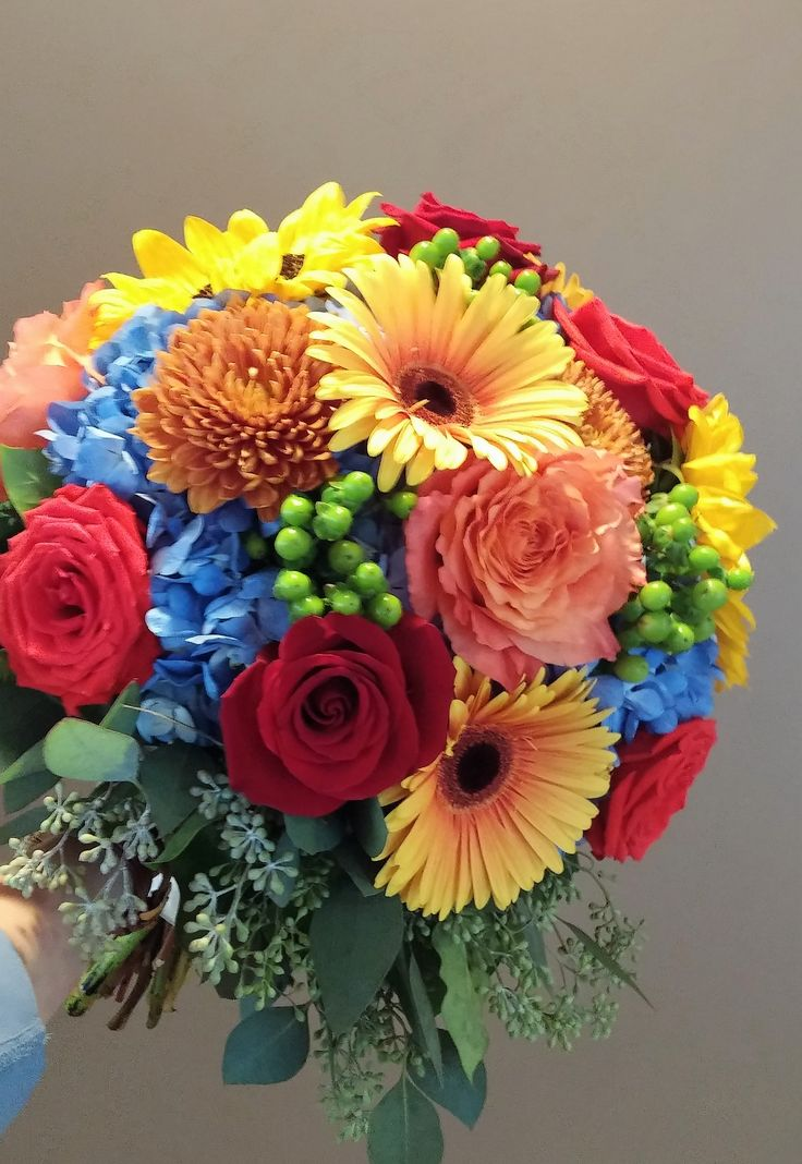 Colorful fall bridal bouquet blue hydrangea green hypericum berries red roses yellow