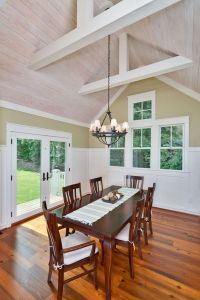 This dining room features a vaulted whitewashed tongue and ...