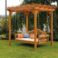 Garden swing under a small wooden pergola near trees ...