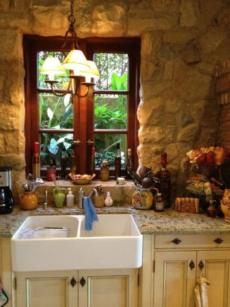 old world french country kitchen The stone wall, wood window and farmhouse sink with