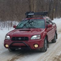 Red subaru baja with blacked out grille, bumper bar and