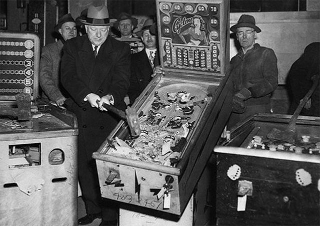 Police beating a pinball machine with a sledge hammer in the 1940s.