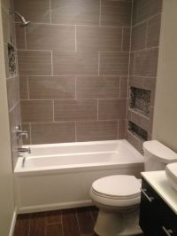 Larger rectangular tiles around a white alcove tub. Ours ...