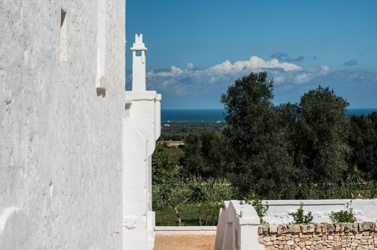 Gorgeous exterior shot of Masseria Le Carrube in Puglia, Italy with blue sky and white stucco walls