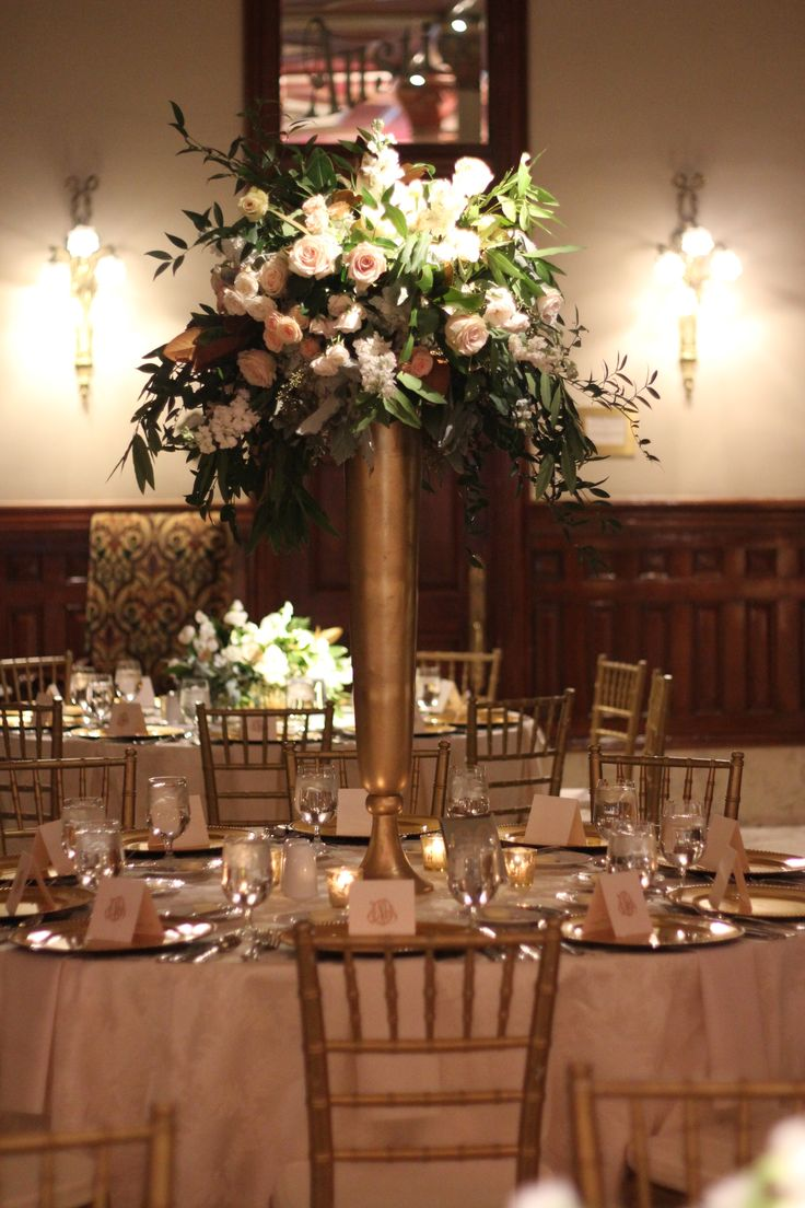 The round tables will have tall gold vases filled with