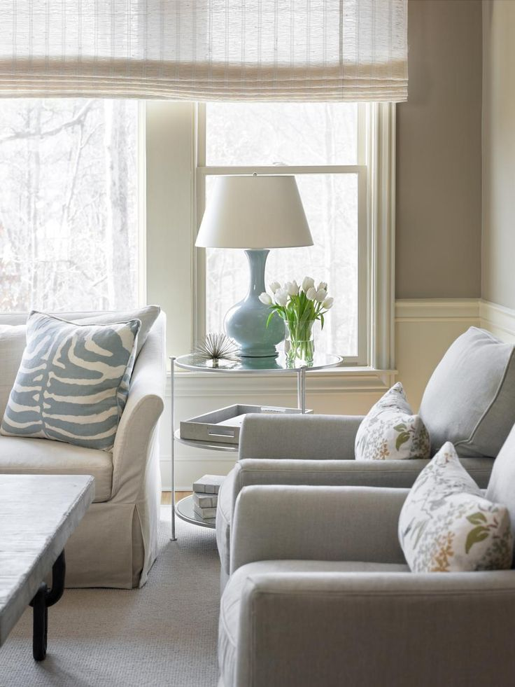 Pale blue accents add soft pretty touches of color to this neutral living room Simple clean