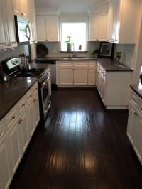 Kitchen - Dark counters, dark floors, white cabinets ...