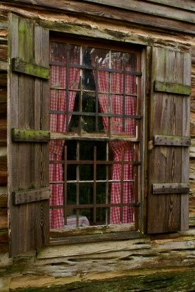 Log Cabin Window with Old Fashioned Shutters and Red and