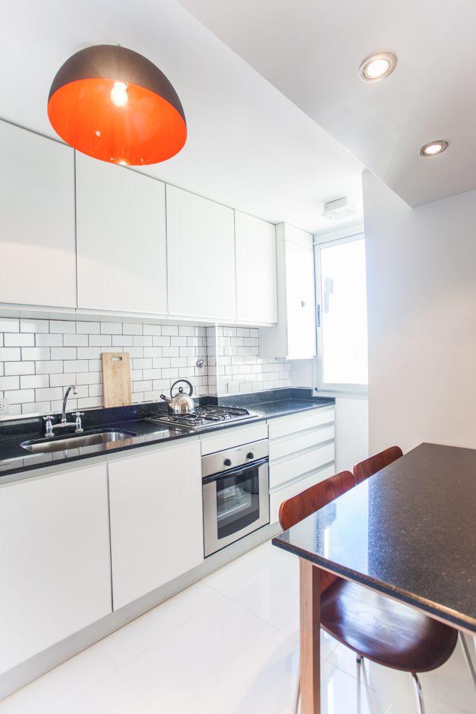 Cocina de muebles blancos mesadas y mesa de granito negro