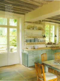 A kitchen with no upper cabinets, plenty of light, and a ...