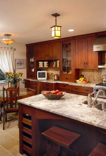 Prairie Style Light Fixtures A Wooden Wheel Table And Cherry Colored Cabinetry With Custom