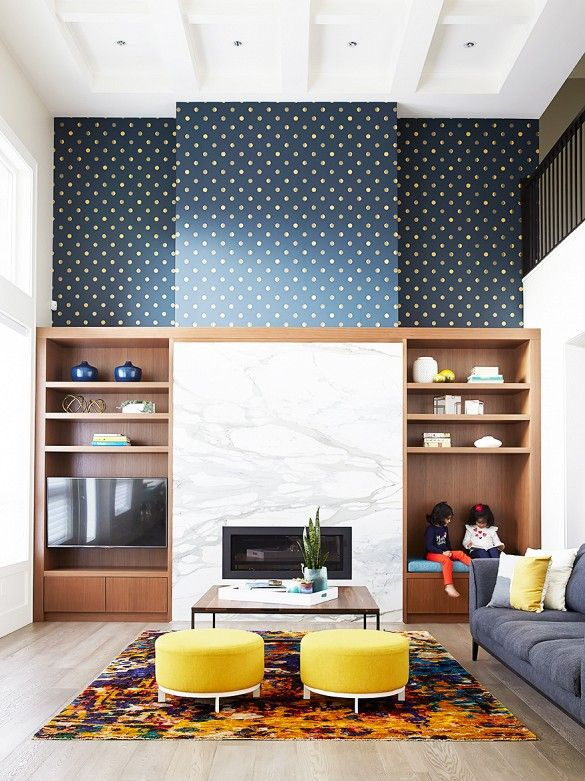 Built-in bookshelves, marble fireplace, and polka dot wallpaper: