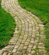 A brick walking path that curves with grass. Stock Photo ...