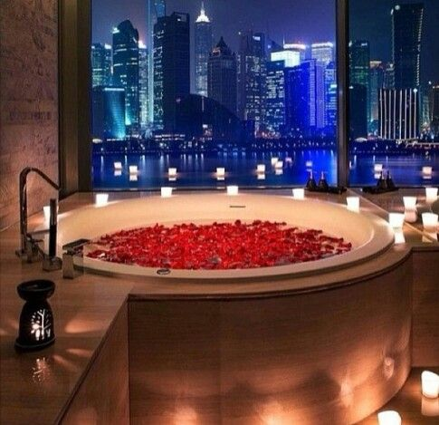 Bathtub full of rose peddles and candles  Romantic