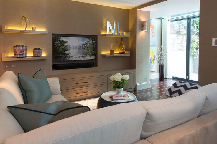 Recessed tv, floating shelves and built-in's matching the wall treatment…comfortable yet sleek. Taylor Howes