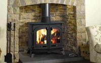 Surrounded by a stone fireplace this wood-burning stove ...
