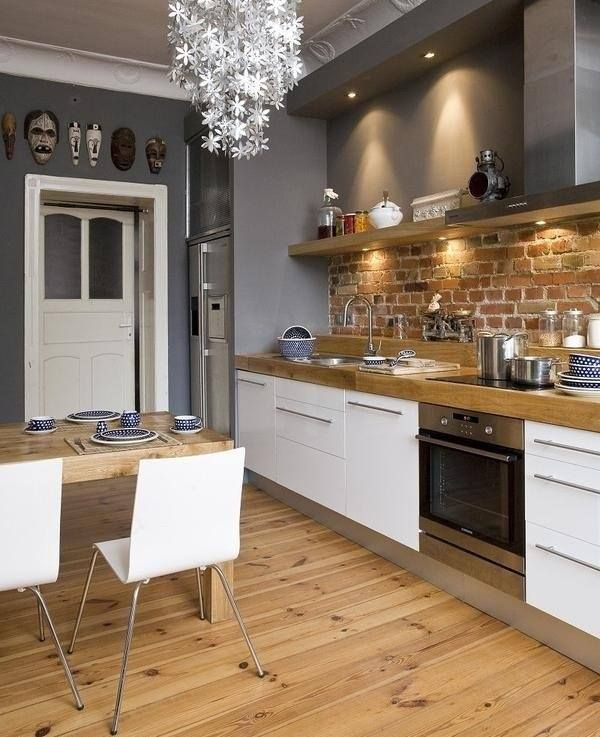 white grey kitchen with exposed brick and natural wood.