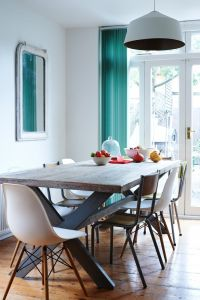 Wood dining room table and teal curtain with white Eames ...