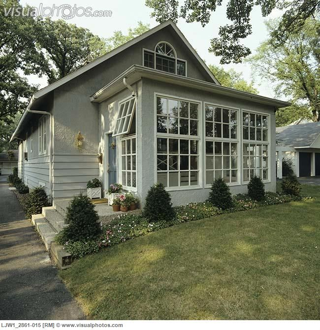 SUNROOMS Front of small grey stucco bungalow addition of sunroom border garden along house