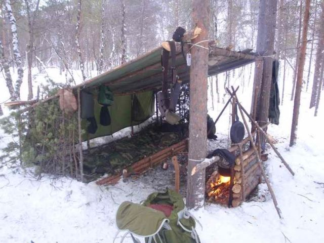 This is how to set up a backwoods camp. I might add an additional tarp to one of the sides to cut down on wind.: