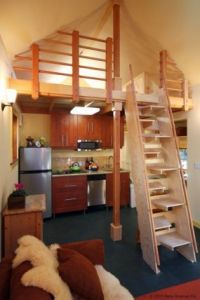 Ladder in small house. Wood railing and small kitchen ...