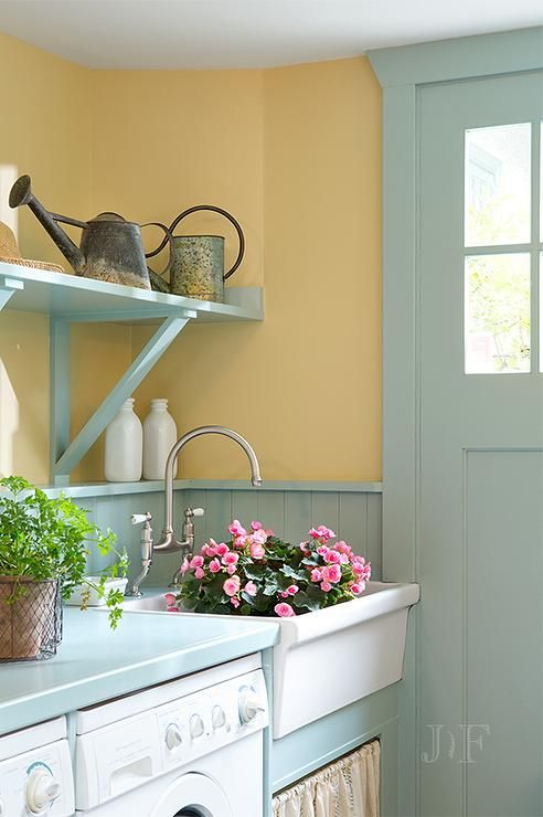 Turquoise mudroom features mustard yellow paint on upper