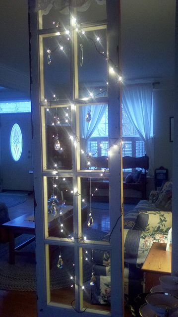 old window used as a room divider string with mini lights