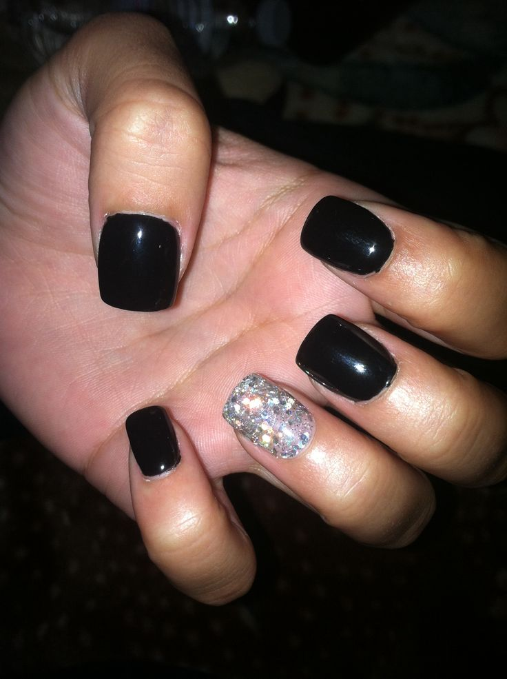 Black gel nails with one silver glitter nail.