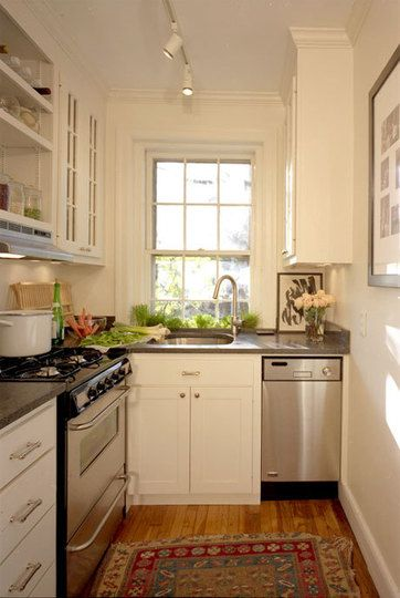 Tiny kitchen. L-shaped. Stainless appliances. Herb window box with sash windows. Gas stove. White cabinets