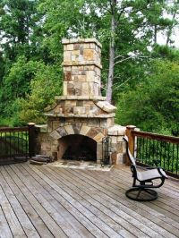 Stone stacked massive corner fireplace on wooden deck ...