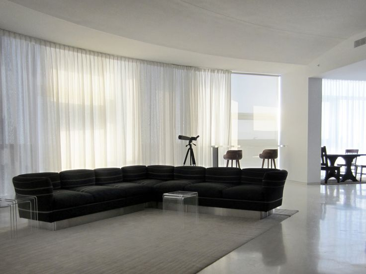 Motorized sheer pinch pleat curtain installed on a curved glass wall  Sheer Curtains