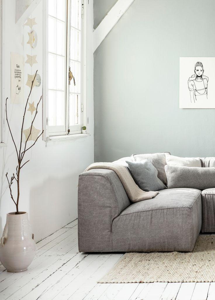 White, grey and light interior / living room with white wooden floors and a grey wall, grey canvas vtwonen couch Lazy, a big