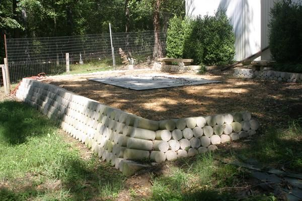 Back patio  a work in progress Retaining wall made from concrete test cylinders in photos by
