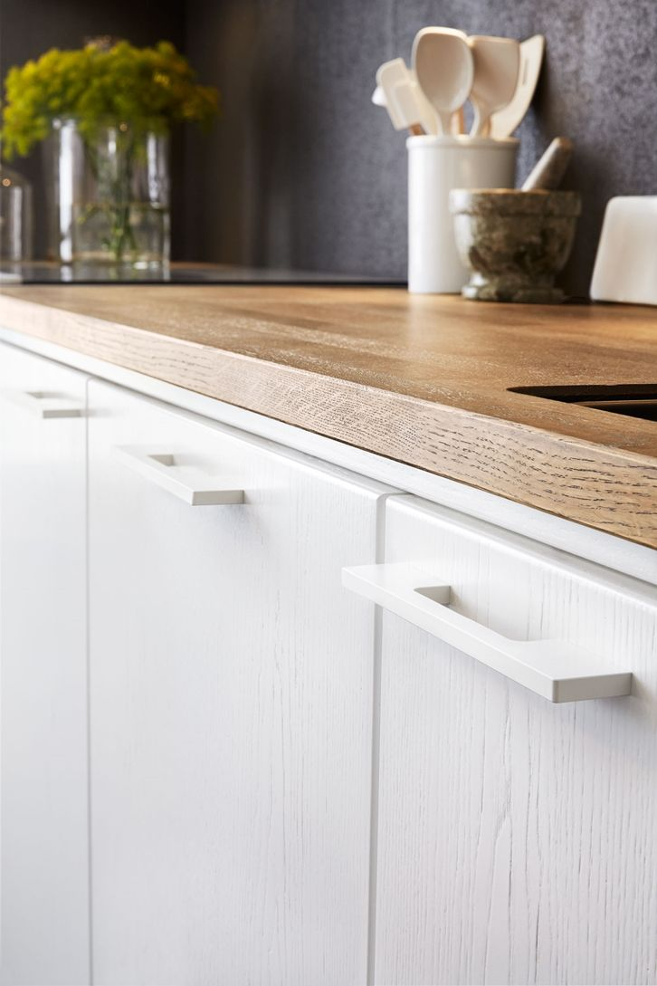 White on white detail wood grain on cabinets rounded edges hardware wooden counter matte