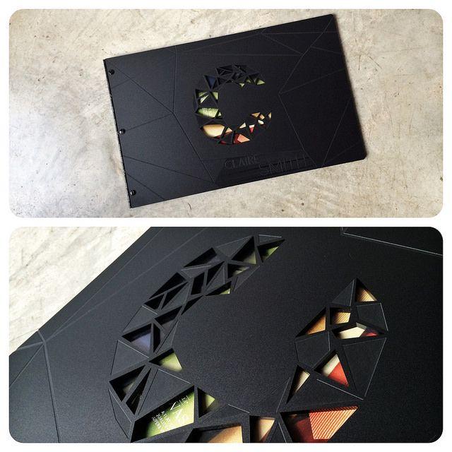 Custom graphic design portfolio book with engraving and cutoutt treatment on matte black