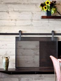Beautiful sliding fireplace screen. The barn door trend is ...