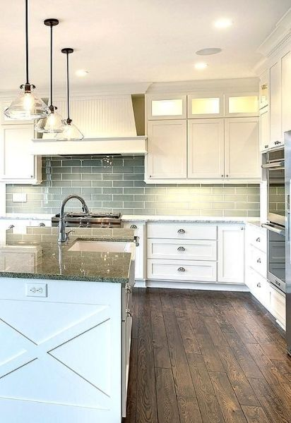 white kitchen with grey granite Three glass pendants hang over a white kitchen island topped with gray granite fitted with a