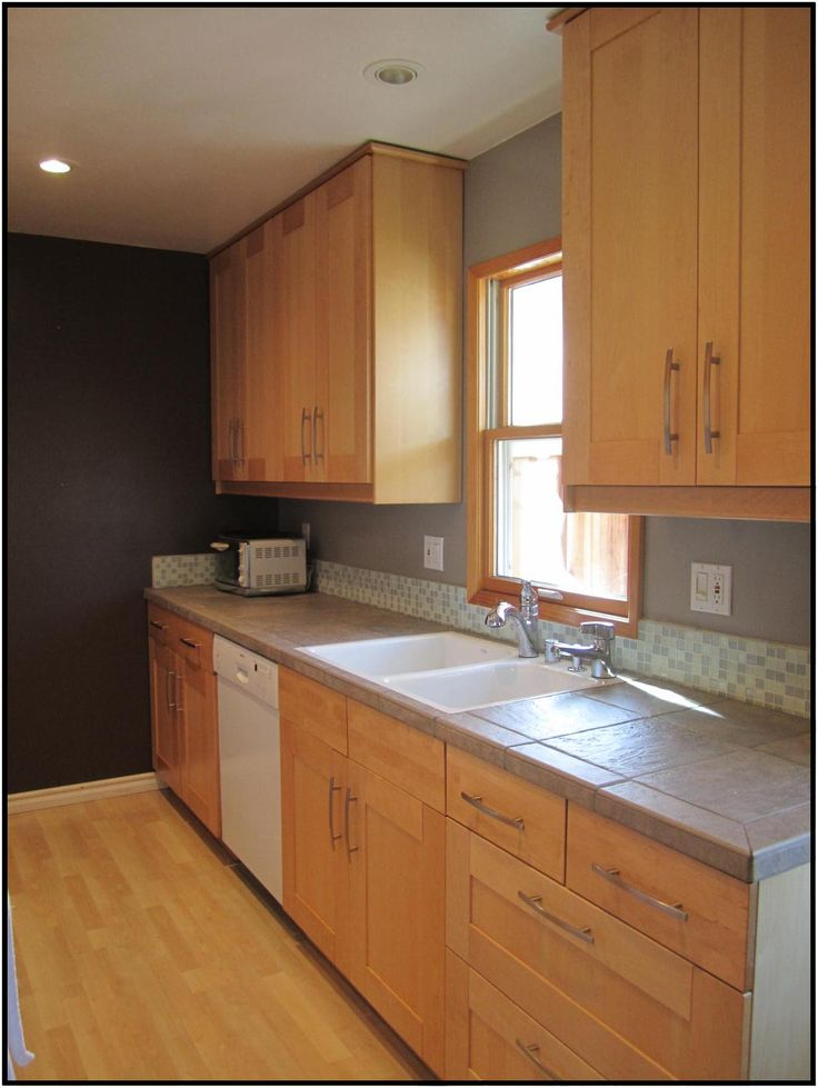 kitchen utensils holder brushed brass faucet maple cabinets, gray counters and short glass backsplash ...