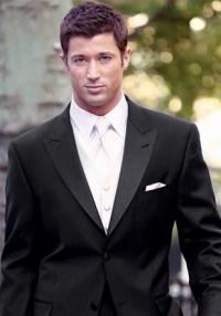 Groom in dark suit, white tie vest, white pocket square ...