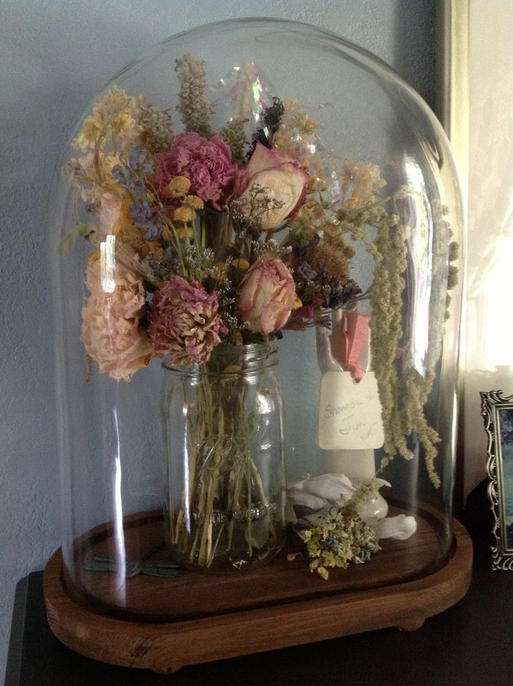 My bridal bouquet dried and covered with a glass cloche