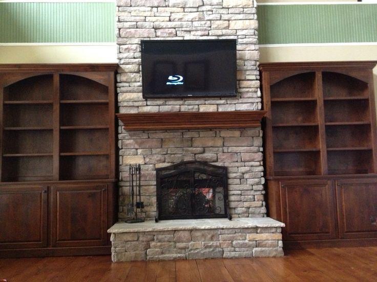 Bookshelves around stone fireplace.