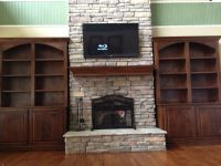Bookshelves around stone fireplace.