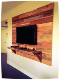 Reclaimed wood accent wall behind mounted TV. www.raw