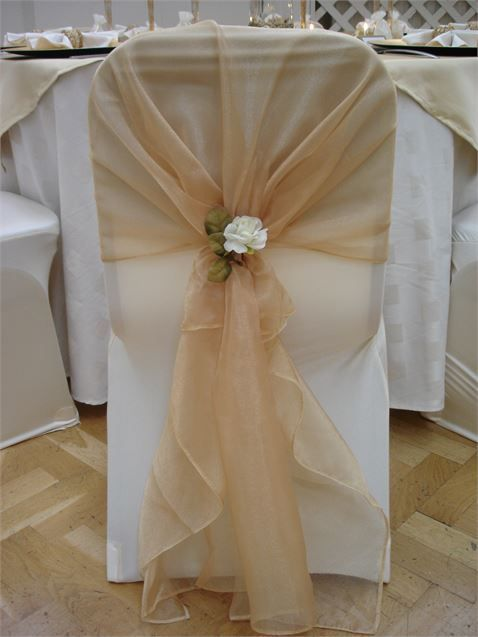Ivory chair cover with gold organza sash and ivory rose