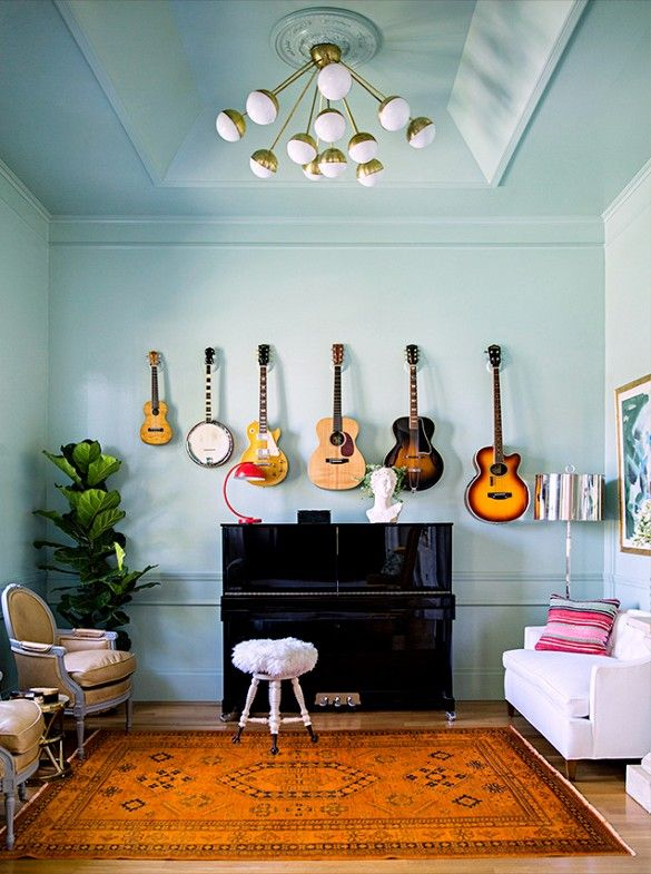How to Display Musical Instruments as Décor‎ | DomaineHome.com // An aqua living room with guitars displayed above a piano.