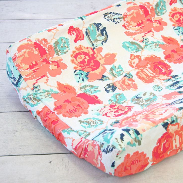 This floral changing pad cover from Caden Lane is the perfect color combination of coral and navy. This changing pad cover stand