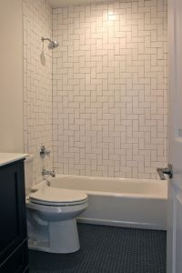 Bathroom with herringbone pattern white subway tile ...