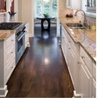 Dark hard wood floors, tan granite, white cabinets ...