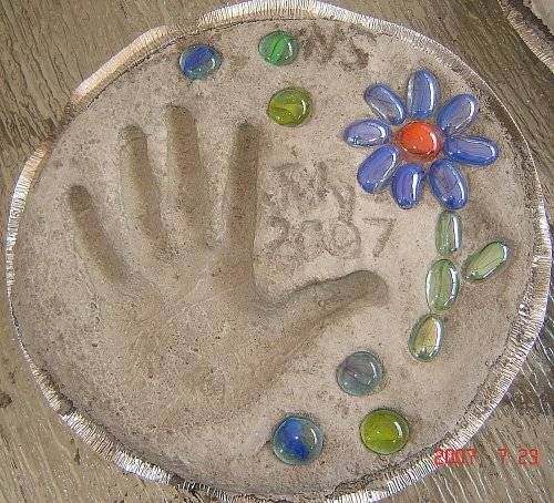 Stepping stone with handprint, flat marbles from Dollar Store, made in disposable aluminum pan used as