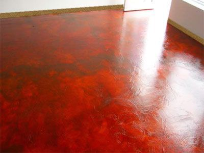 Artists studio floor  concrete floor with textured overlay and stains and dyes in rich red